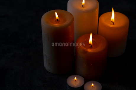 Candle lights in the darkness. Some candles burning in dark background.の写真素材 [FYI04272589]