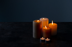 Candle lights in the darkness. Some candles burning in dark background.の写真素材 [FYI04272602]