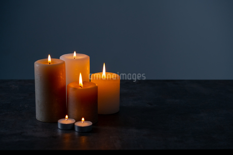 Candle lights in the darkness. Some candles burning in dark background.の写真素材 [FYI04272611]