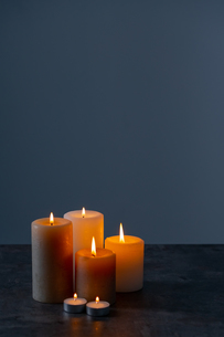 Candle lights in the darkness. Some candles burning in dark background.の写真素材 [FYI04272632]