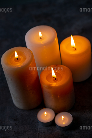 Candle lights in the darkness. Some candles burning in dark background.の写真素材 [FYI04272634]