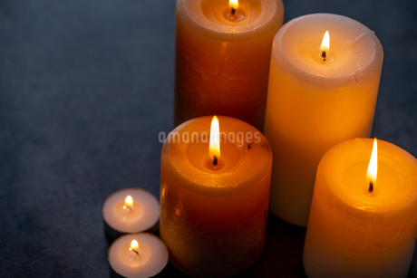 Candle lights in the darkness. Some candles burning in dark background.の写真素材 [FYI04272655]