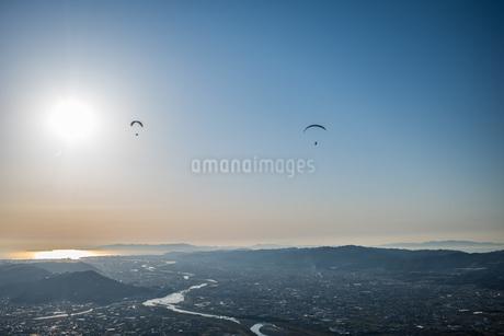夕日に向かって飛ぶパラグライダーの写真素材 [FYI04281410]