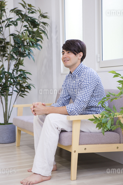 ソファに座る男性の写真素材 [FYI04281518]