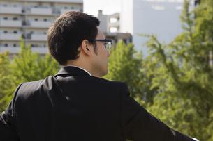 屋上から外を眺めるビジネスパーソンの写真素材 [FYI04281852]