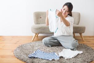 ベビー服を見る妊婦さんの写真素材 [FYI04282077]