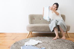 ベビー服を見る妊婦さんの写真素材 [FYI04282082]