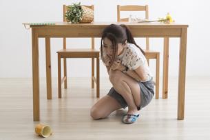 地震でテーブル下に避難する女性の写真素材 [FYI04282117]