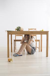 地震でテーブル下に避難する女性の写真素材 [FYI04282118]