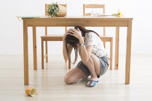 地震でテーブル下に避難する女性の写真素材 [FYI04282119]