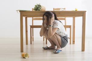 地震でテーブル下に避難する女性の写真素材 [FYI04282121]