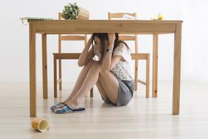 地震でテーブル下に避難する女性の写真素材 [FYI04282122]