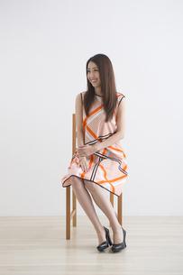 椅子に座るワンピースの女性の写真素材 [FYI04282135]