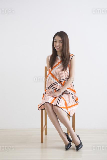 椅子に座るワンピースの女性の写真素材 [FYI04282137]