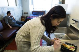 お弁当を作る女性と見守る男性の写真素材 [FYI04282487]