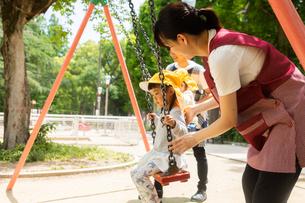 公園で遊ぶ保育士と園児たちの写真素材 [FYI04282806]