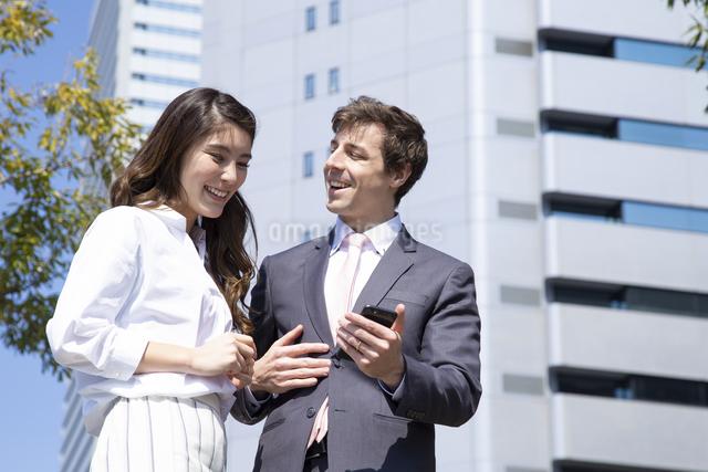 スマホを見るビジネスマンとビジネスウーマンの写真素材 [FYI04282863]