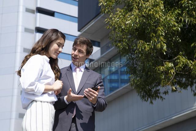 スマホを見るビジネスマンとビジネスウーマンの写真素材 [FYI04282866]