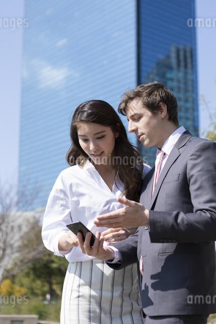 スマホを見るビジネスマンとビジネスウーマンの写真素材 [FYI04282867]
