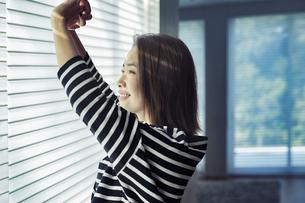 部屋のブラインドを開けストレッチをする女性の写真素材 [FYI04282926]
