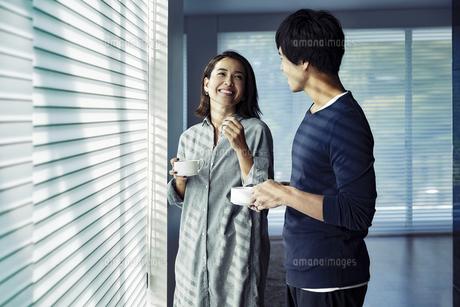朝日を浴びながらコーヒーを飲む夫婦の写真素材 [FYI04282927]