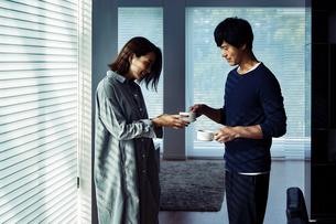 朝日を浴びながらコーヒーを渡す夫婦の写真素材 [FYI04282931]