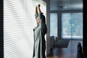 部屋のブラインドを開けストレッチをする女性の写真素材 [FYI04282932]