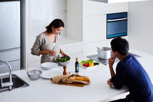 キッチンで料理する女性と眺める男性の写真素材 [FYI04282933]