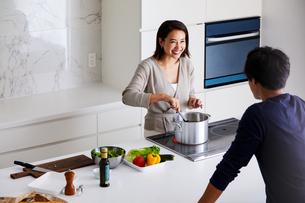 キッチンで料理する女性と眺める男性の写真素材 [FYI04282934]
