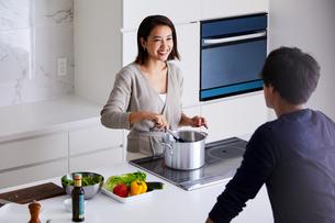 キッチンで料理する女性と眺める男性の写真素材 [FYI04282935]