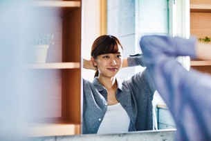 鏡の前で髪を束ねる20代女性の写真素材 [FYI04282936]