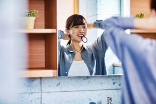 鏡の前で髪を束ねる20代女性の写真素材 [FYI04282937]