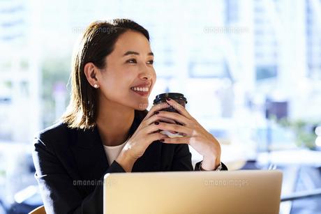 コーヒーを飲みながらカフェで仕事をするビジネスウーマンの写真素材 [FYI04282939]