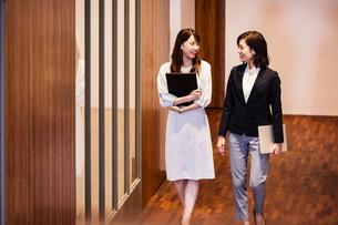 オフィスを会話しながら歩くビジネスウーマンの写真素材 [FYI04282940]