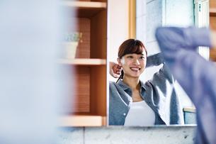 鏡の前で髪を束ねる20代女性の写真素材 [FYI04282941]