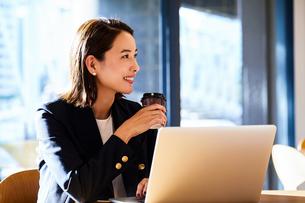 コーヒーを飲みながらカフェで仕事をするビジネスウーマンの写真素材 [FYI04282942]