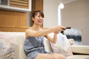 ソファに座ってチャンネルを変えている女性の写真素材 [FYI04283420]