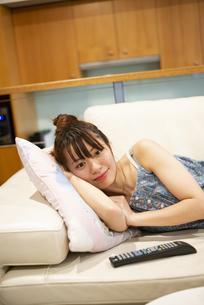 ソファに寝そべってテレビを見ている女性の写真素材 [FYI04283438]
