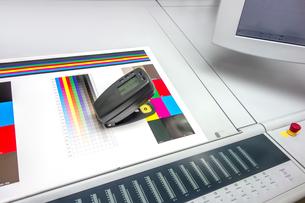 印刷物を測色機で品質管理するイメージ。印刷業、品質管理イメージの写真素材 [FYI04284053]