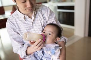 父親にミルクを飲ませてもらう赤ちゃんの写真素材 [FYI04284277]