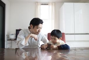 一緒にスマホを見る男の子と父親の写真素材 [FYI04284285]