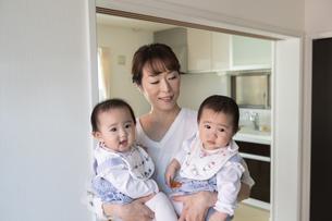 双子の赤ちゃんを抱く母親の写真素材 [FYI04284334]