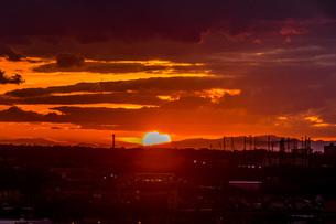 夕焼けの中、雲に挟まれた太陽の写真素材 [FYI04285313]