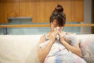 ソファの上で鼻をかんでいる女性の写真素材 [FYI04286444]