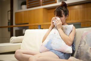 ソファの上で泣いている女性の写真素材 [FYI04286446]