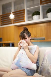 ソファの上で泣いている女性の写真素材 [FYI04286447]