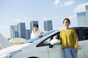 車の前に立つ笑顔の20代男女の写真素材 [FYI04286598]