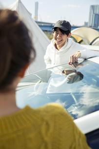 車の前に立つ笑顔の20代男女の写真素材 [FYI04286601]