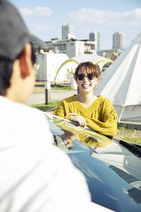 車の前に立つ笑顔の20代男女の写真素材 [FYI04286602]