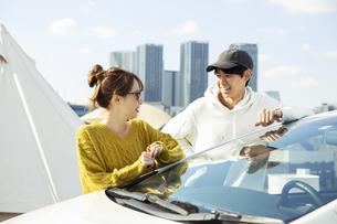 車の前に立ち笑顔で話す20代男女の写真素材 [FYI04286657]